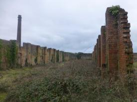 View from inside the remains of the former nitric acid factory to its chimney (the chimney is listed at Grade II)